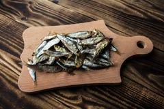 在木背景的熏制的西鲱 免版税库存图片