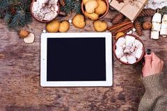 在木背景的片剂和圣诞节装饰 免版税库存图片