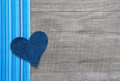 在木背景的牛仔布蓝色心脏 免版税库存照片