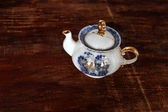 在木背景的瓷茶壶 免版税库存照片