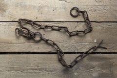 在木背景的生锈的老金属链子 免版税图库摄影