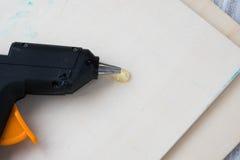 在木背景的电热的胶水枪 修理或创造性背景的概念 库存图片