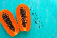在木背景的番木瓜果子 切片在木背景的甜番木瓜,与叶子的被对分的番木瓜, 免版税图库摄影