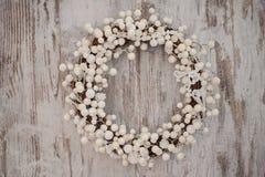 在木背景的白色圣诞节装饰花圈 免版税库存照片