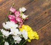在木背景的白色桃红色和黄色花 免版税库存照片