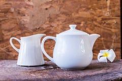 在木背景的白色茶罐 库存图片