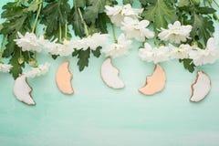 在木背景的白色菊花用一个自创曲奇饼以一个月的形式,与写或adve的空的空间 免版税库存照片