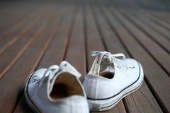 在木背景的白色鞋子 免版税库存照片