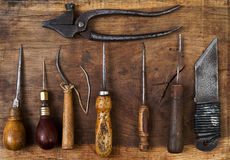 在木背景的皮革工艺工具 Craftmans工作书桌 片断皮和运转的手工制造工具 顶视图 库存照片