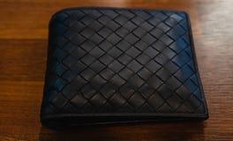 在木背景的皮革钱包黑色皮革 免版税图库摄影