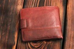 在木背景的皮革钱包 免版税库存照片