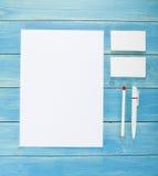 在木背景的空白的文具 包括名片、A4信头、笔和铅笔 免版税库存照片