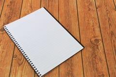 在木背景的空白的笔记本 免版税库存照片