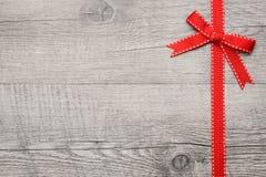 在木背景的红色丝带和弓 免版税库存照片
