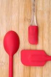 在木背景的红色厨房器物 免版税库存图片