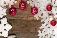 在木背景的红色圣诞节球在白色雪花和杉木附近 invitation new year 框架 顶视图 免版税库存照片
