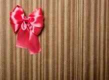 在木背景的红色弓 免版税库存图片