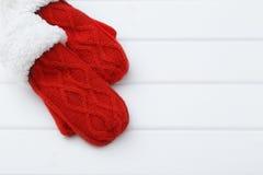 在木背景的红色手套 免版税库存图片