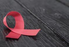 在木背景的红色艾滋病了悟丝带 库存照片