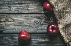 在木背景的红色苹果与袋装 果子,自然食物 免版税库存照片