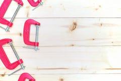 在木背景的红色c钳位 免版税库存照片
