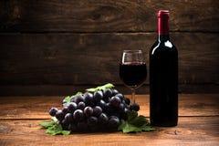 在木背景的红葡萄酒 免版税库存图片