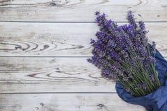 在木背景的纸包裹的紫色淡紫色花束 库存图片