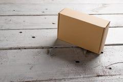 在木背景的纸板箱 免版税库存照片