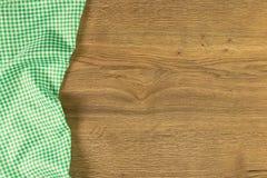 在木背景的绿色方格的布料餐巾 免版税库存照片