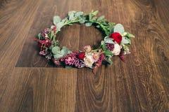 在木背景的美丽的婚礼红色玫瑰花冠 免版税库存图片
