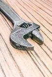 在木背景的老普遍可调扳手 特写镜头长凳工具 免版税库存照片