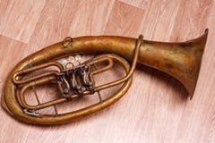 在木背景的老生锈的女低音saxhorn 库存照片
