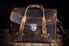 在木背景的老皮包 库存照片