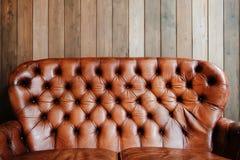在木背景的老皮革沙发,空 库存照片