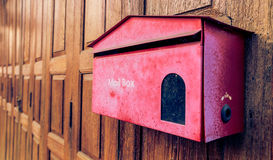 在木背景的老红色邮箱 库存照片