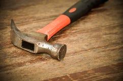 在木背景的老红色锤子 库存照片
