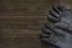 在木背景的老肮脏的皮革工作手套 库存照片