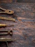 在木背景的老葡萄酒手工具 库存图片