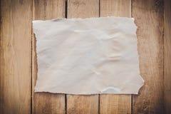 在木背景的老被撕毁的纸 免版税图库摄影