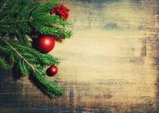 在木背景的自然冷杉分支和一棵新年` s杉树玩具 新年度`s背景 免版税库存照片