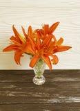 在木背景的花瓶橙色百合乡情装饰构成 图库摄影