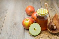 在木背景的苹果计算机和蜂蜜瓶子 犹太Rosh hashana (新年)假日 免版税库存照片