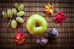 在木背景的苹果绿的秋叶 免版税库存图片