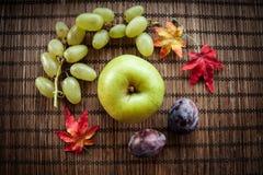 在木背景的苹果绿的秋叶 免版税图库摄影