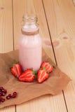 在木背景的草莓奶昔 免版税库存图片