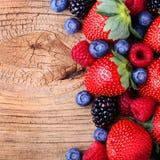 在木背景的莓果 草莓,蓝莓 库存照片