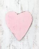 在木背景的葡萄酒桃红色心脏 免版税库存照片