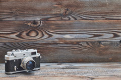 在木背景的葡萄酒老减速火箭的测距仪照相机 免版税库存图片