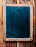 在木背景的葡萄酒黑板。 免版税库存照片