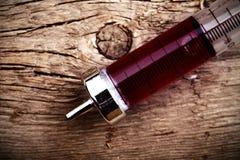 在木背景的葡萄酒玻璃注射器 库存照片
